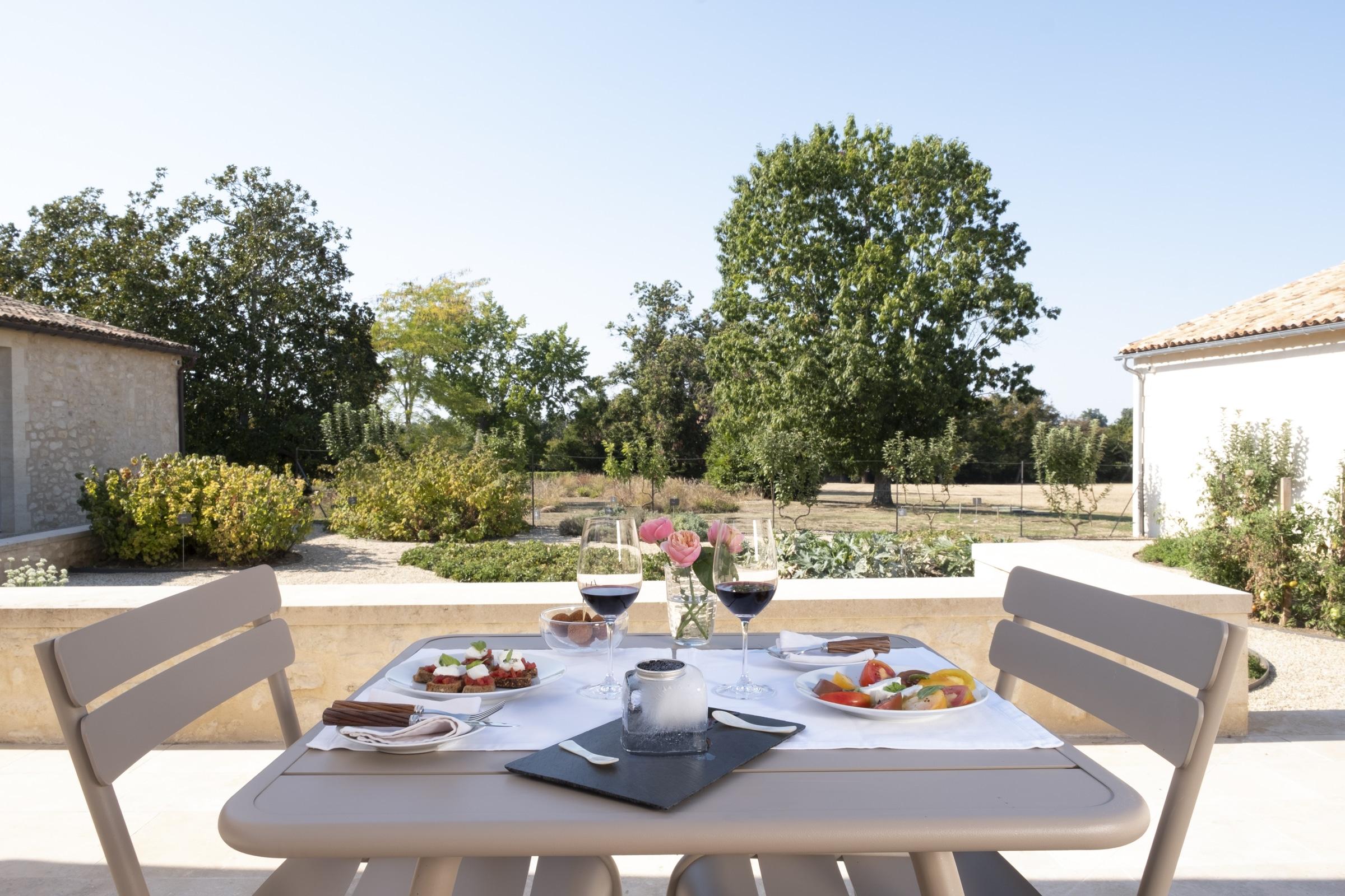 petits plats maison et verres de vin servis sur la terrasse du chateau avec vue sur le potager